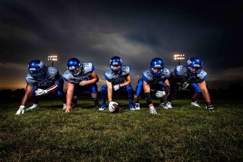 Fünf Footballspieler hocken am Rasen