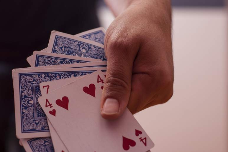 Jemand hält Spielkarten in der Hand